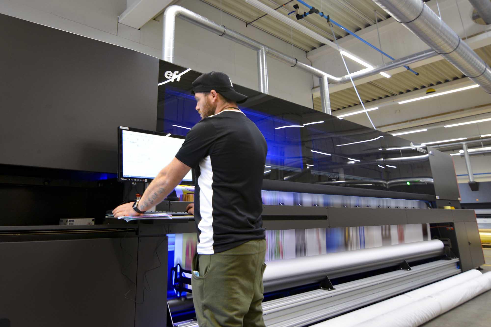 Mann steht vor einer großen Druckmaschine